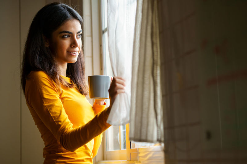 Side view of young woman drinking coffee by window