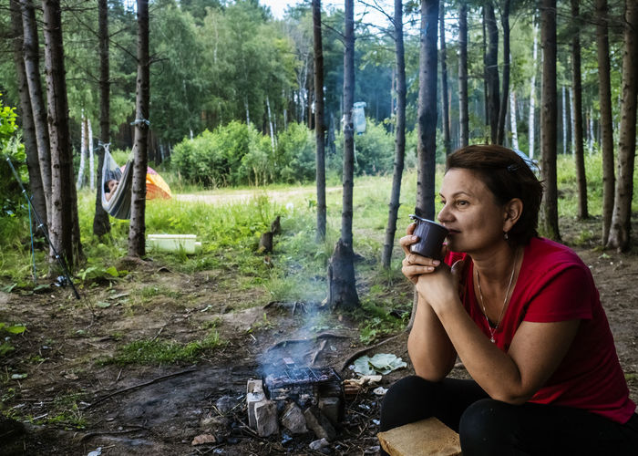 Smiling woman drinking coffee while sitting in forest
