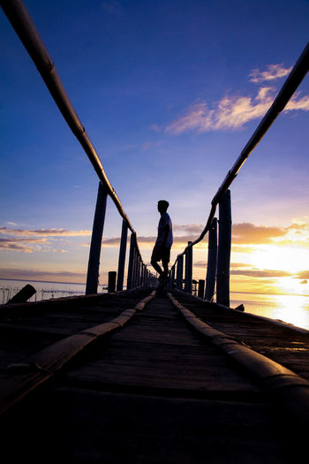 Silhouette man standing on jetty against sea at sunset
