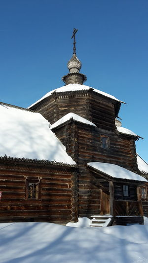 Old wooden church in the open air museum of Suzdal', Russia Sky Built Structure Architecture Building Exterior Building Low Angle View Nature Cold Temperature Snow No People Winter Place Of Worship Day Belief Religion Spirituality Blue Clear Sky Roof Outdoors Spire  Open Air Museum Church Architecture Wooden Church  Landmark Building