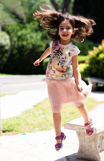 Portrait Of Happy Girl Jumping On Footpath