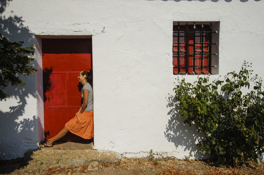 Architecture Building Exterior Built Structure Cliche Day Flower Freedom Girl Girl In Doorway House Laughing Outdoors Plant Profile Shot Red Door Residential Building SPAIN Travel Travelling Window Window Box Young And Free Young Woman