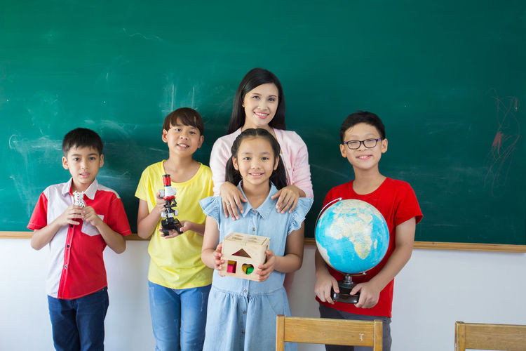 Portrait of smiling students and teacher standing against blackboard in classroom