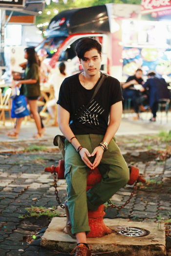 Portrait of young man sitting on footpath
