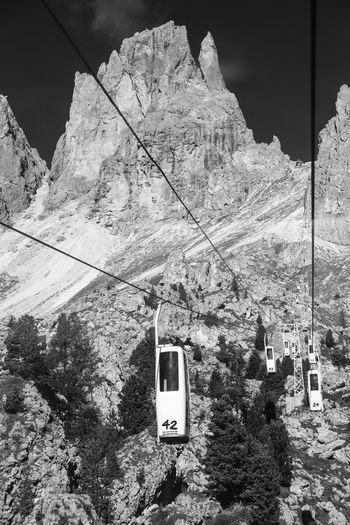 Low angle view of overhead cable car against rocky mountains