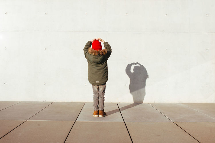 Rear view of boy with shadow on wall