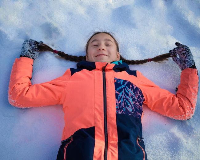 Cute girl lying in snow