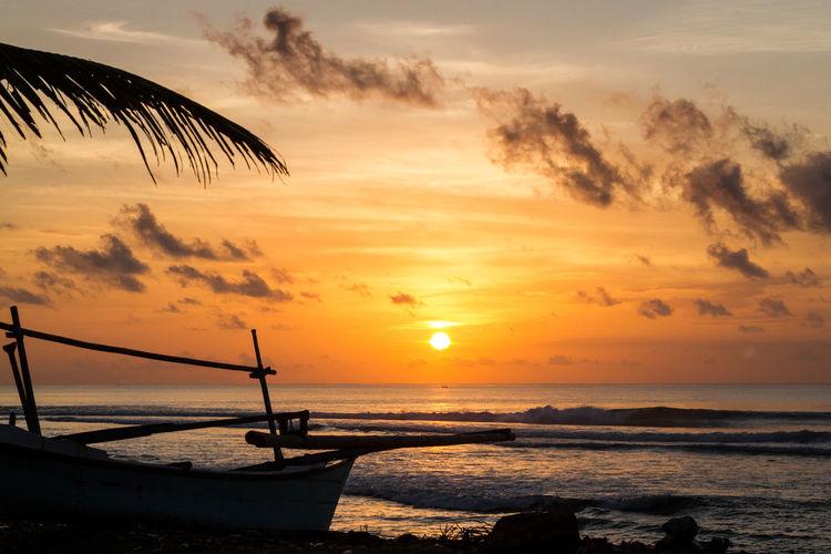 Boat anchored by sea at dusk