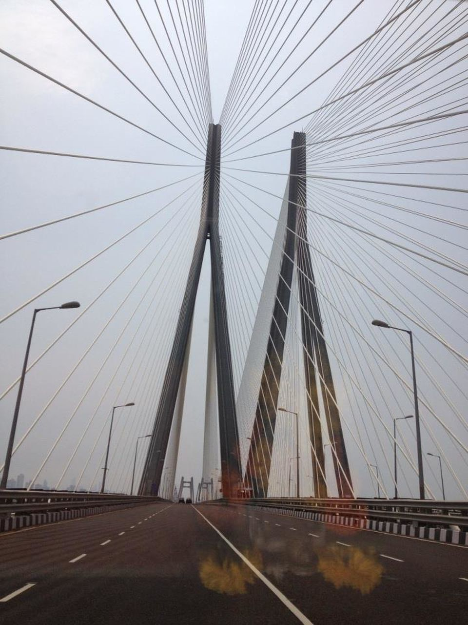 suspension bridge, connection, transportation, bridge - man made structure, architecture, engineering, built structure, travel, travel destinations, the way forward, outdoors, bridge, day, city, cable, sky, road, no people, skyscraper, urban skyline, line