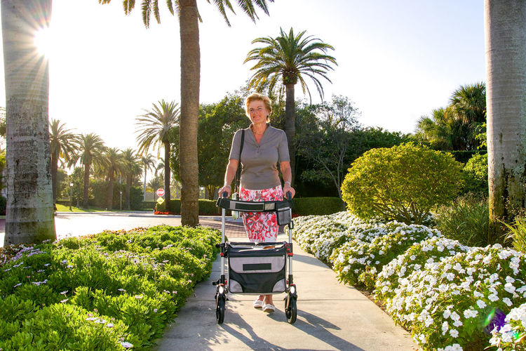 Full length of woman with walker on footpath at park