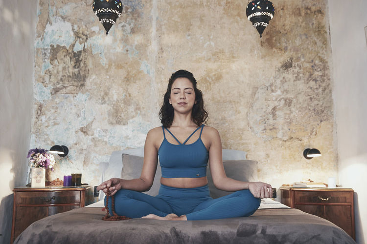 Woman meditating while sitting on bed at home