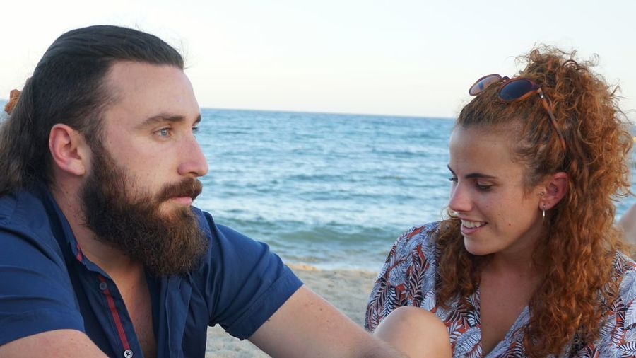 Portrait of smiling young couple on beach against sky