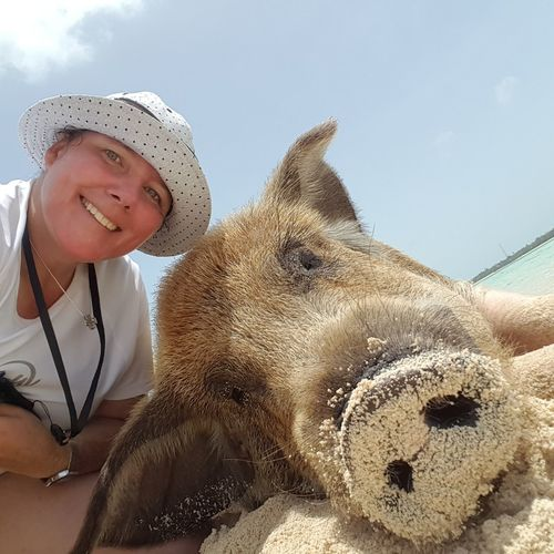 Close-up portrait of smiling woman with pig against sky