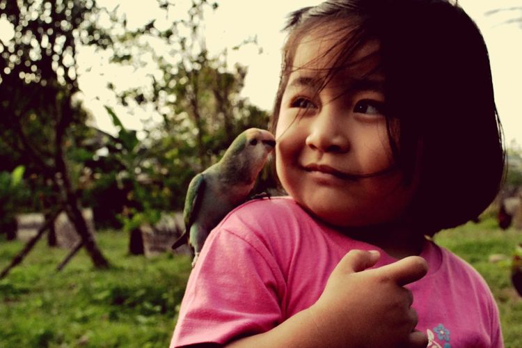 Close-Up Of Girl With Bird On Shoulder At Park