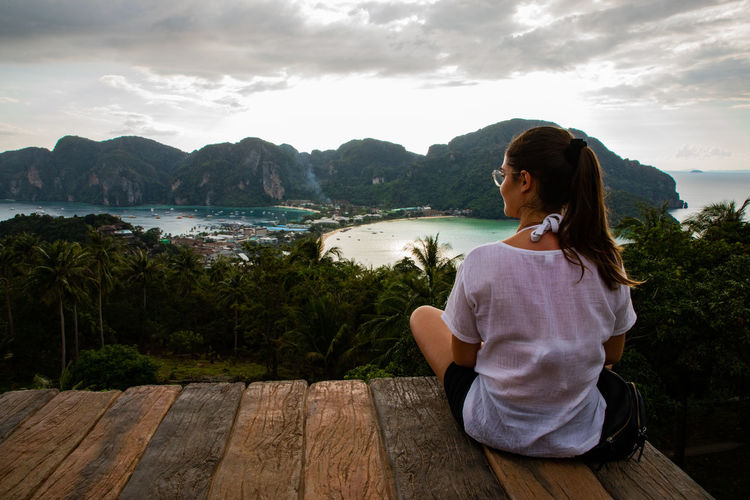 Rear view of woman sitting at observation point against sea