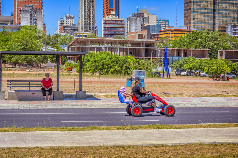 Costanera de Asuncion Backseat Riding  Children Costanera De Asunción Paraguay-Asuncion Adult Architecture Backseat Building Exterior Built Structure Bus Stop City City Life Day Land Vehicle Motorcycle Outdoors People Real People Sky Skyscraper Street Transportation Tree Two People