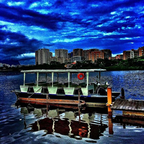 Pier in river against cloudy sky