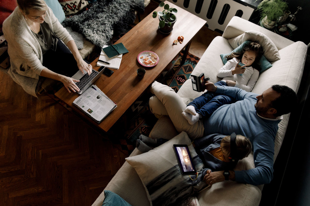 HIGH ANGLE VIEW OF PEOPLE SITTING ON SOFA IN BEDROOM
