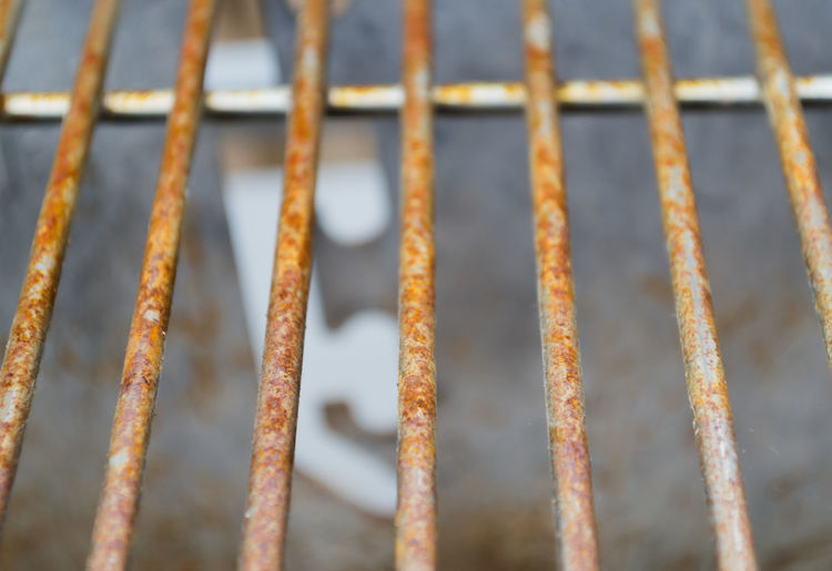 Rusted metal grill bars pictured vertically showing signs of deterioration Backgrounds Barrier Boundary Brown Close-up Day Fence Focus On Foreground Full Frame Metal Nature No People Outdoors Pattern Railing Rusty Security Selective Focus Textured  Weathered Wheel