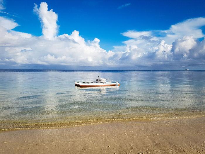 Boat on the beach Water Nautical Vessel Sea Beach Yacht Blue Sailing Ship Sand Reflection Sky Seascape The Great Outdoors - 2018 EyeEm Awards The Traveler - 2018 EyeEm Awards Capture Tomorrow