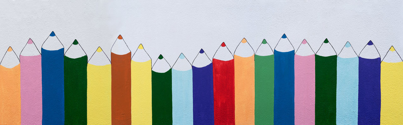 Row of painted, different colored crayons on a white wall Colored Pencil Creativity Kindergarten Learning Nursery School Paint Panoramic Preschool Wall Background Childish Colorful Crayon Creative Draw Education Header Kiddy Learn Many Pencil Row School Side By Side Vertical