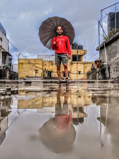 Reflection of man with umbrella in water