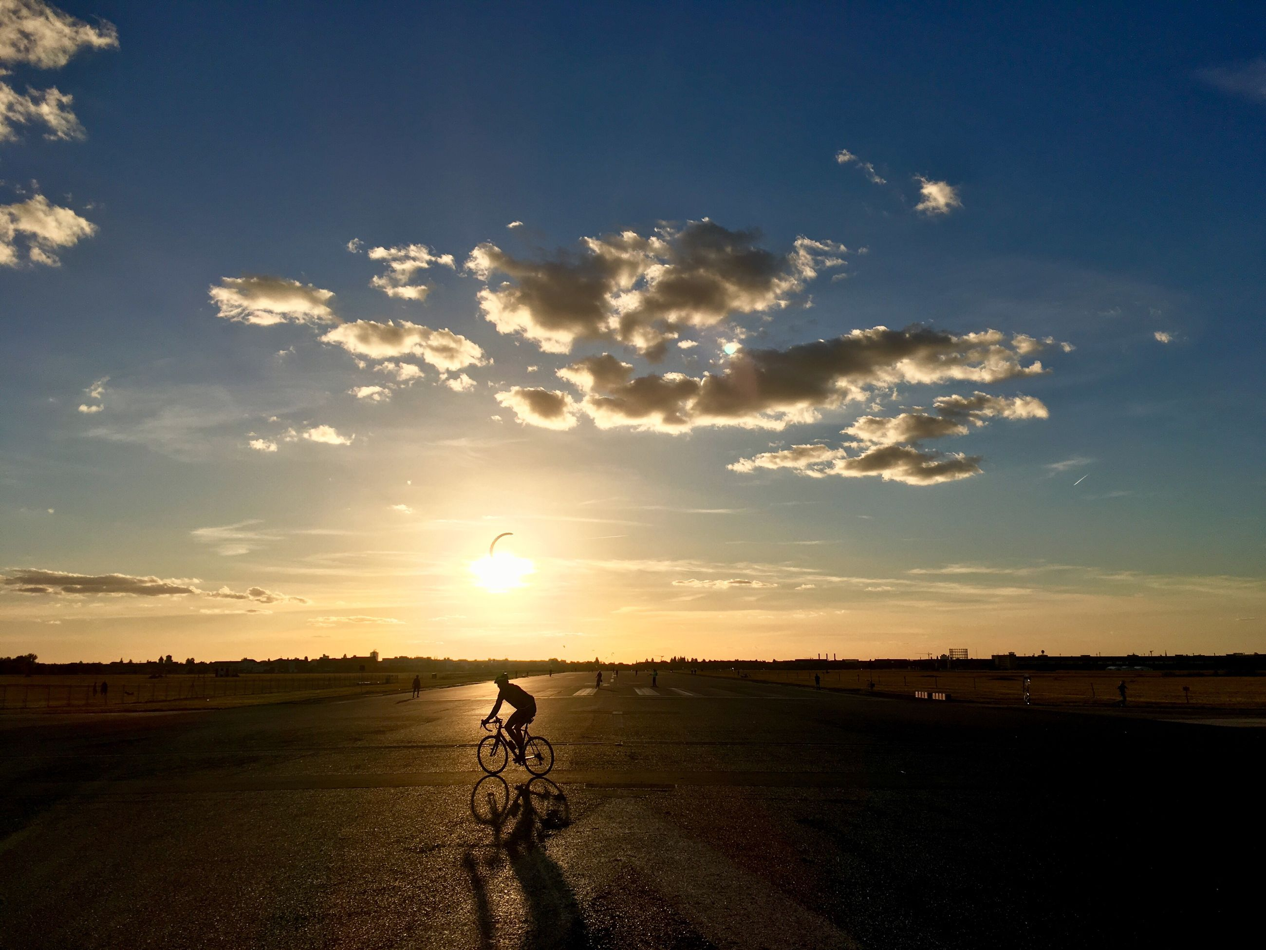 sky, sunset, cloud - sky, landscape, beauty in nature, land, real people, field, lifestyles, nature, environment, leisure activity, scenics - nature, bicycle, transportation, one person, riding, ride, sunlight, outdoors, sun