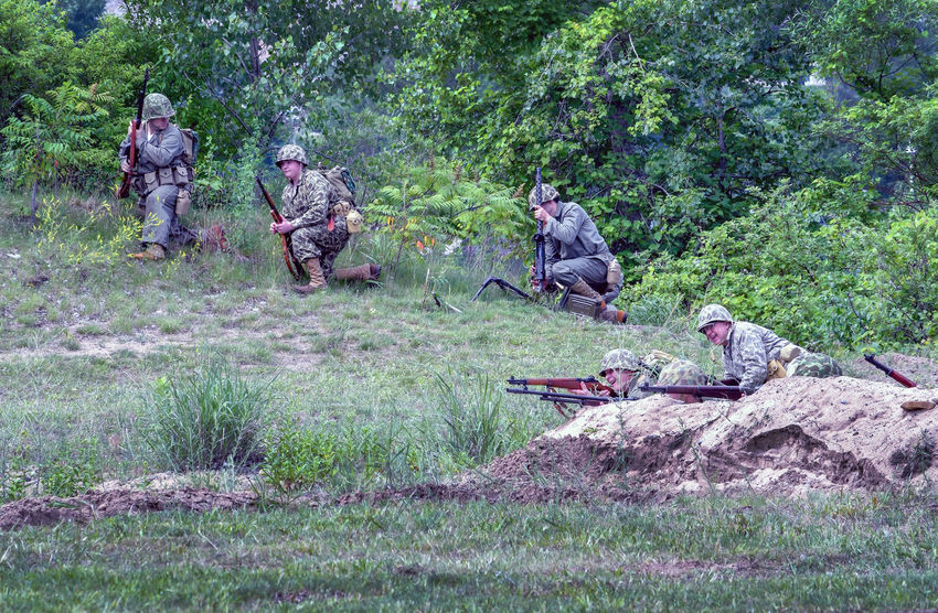 June 22 2018 St Joseph MI USA ; soldiers in vintage uniforms from the korean and vietnam war, act in a mock battle during this reenactment in Michigan USA Event Field Fight Korean War Lest We Forget Nature Soldiers Uniforms Active Adults America Camouflage Clothing Editorial  Historiacl Reenactment History Men Military Outdoors People Reenactment Role Playing St Joseph MI USA Vietnam War Era Vintage Uniforms War Weapons