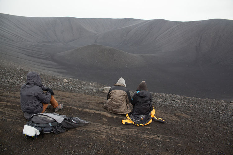 Rear view of tourists sitting on barren landscape