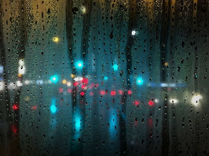 Illuminated lights seen through wet window during rainy season