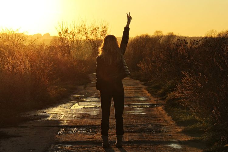 Rear View Of Woman Gesturing Peace Sign While Standing On Road Against Sky During Sunset