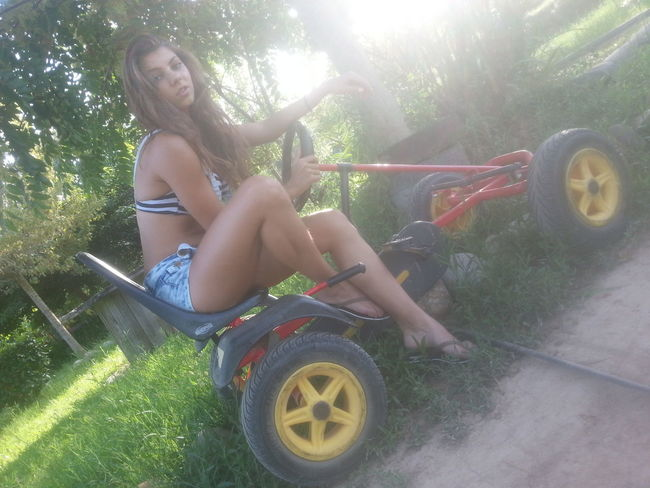 Young Women Water Spraying Smiling Summer Happiness Fun Full Length Lens Flare Grass Car Wash