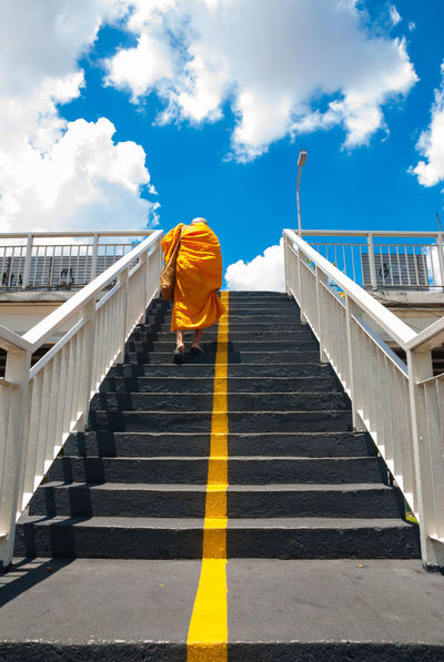 Buddhist's Monks steps up the stairs of the pedestrian overpass in the city. Bridge Buddhist's Monks Cloud - Sky Day Fence Footbridge Crossing One Person Outdoors Overpass View Pedestrian Crossing Railing Sky Staircase Steps Steps And Staircases Steps And Stairs The City Light Urban Walkway Yellow Robe