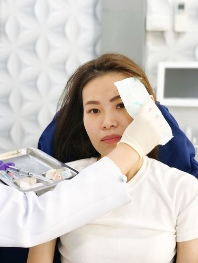 Cropped hand operating woman while sitting on chair