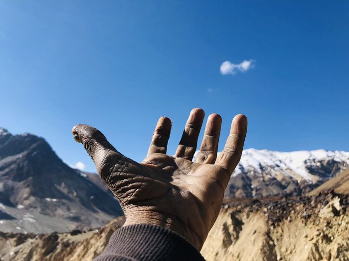 Cropped hand of man gesturing towards mountains and blue sky