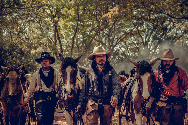 Cowboys standing with horse in forest