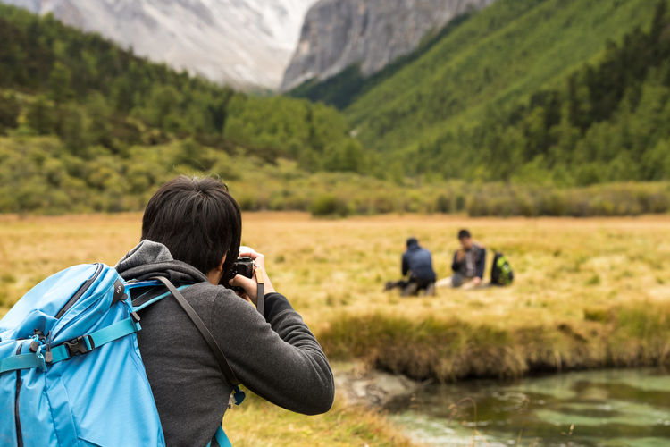 Daocheng,Yading Adventure Backpack Beauty In Nature Camera - Photographic Equipment Day Field Grass Hiking Landscape Leisure Activity Lifestyles Men Mountain Mountain Range Nature One Person Outdoors Photographer Photographing Photography Themes Real People Rear View Scenics Technology Women Connected By Travel Connected By Travel