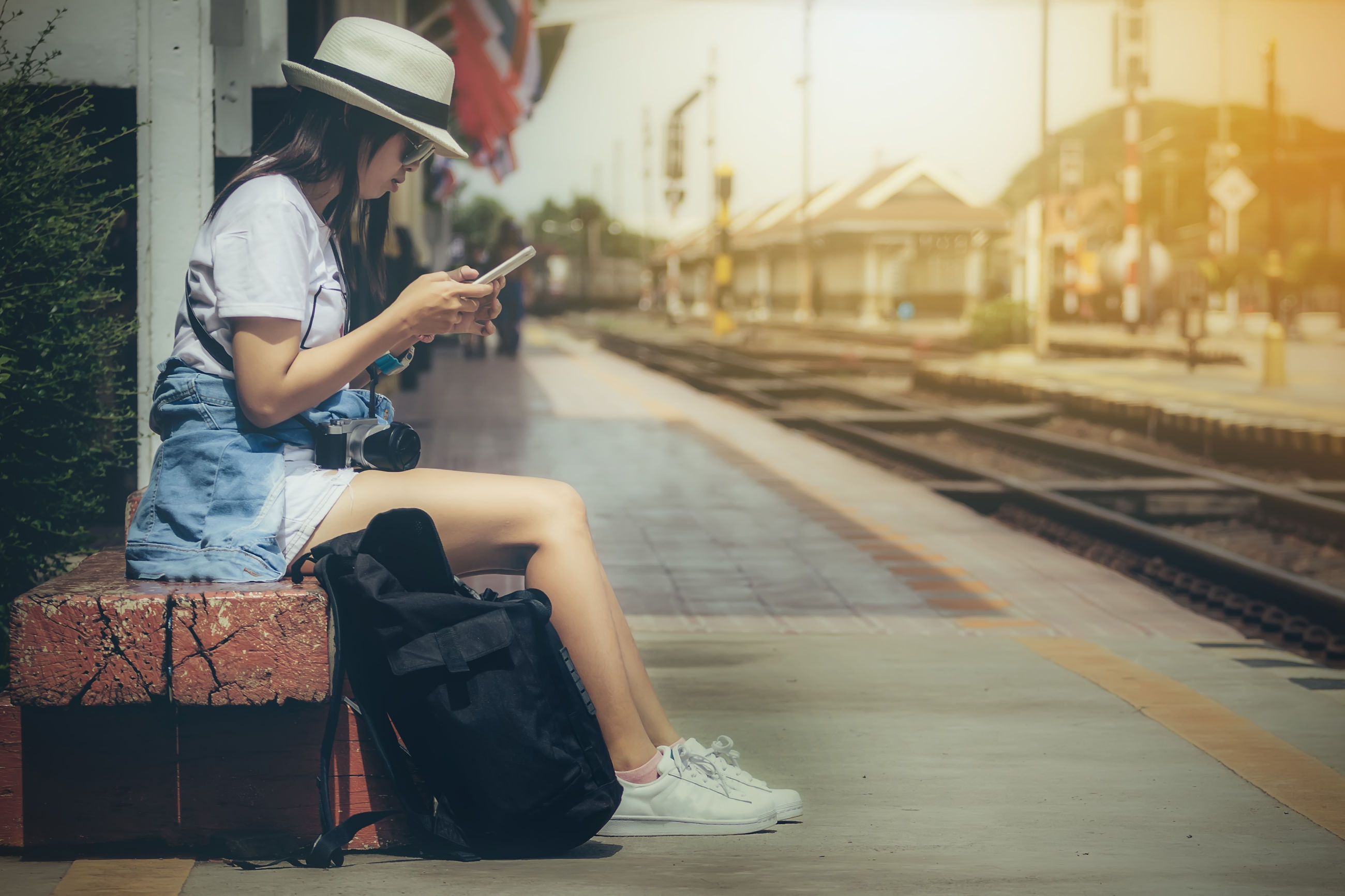 FULL LENGTH OF MAN SITTING ON RAILROAD PLATFORM