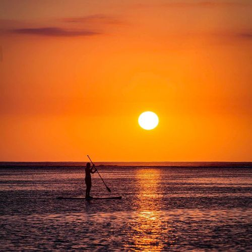 Silhouette man paddleboarding in sea against orange sky