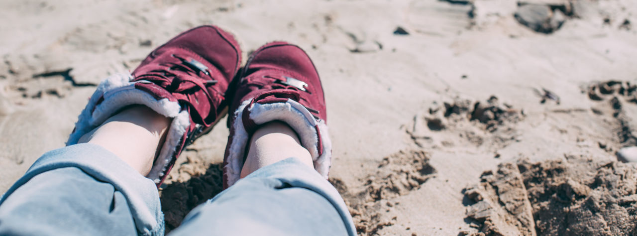 Low section of woman wearing shoes on sand