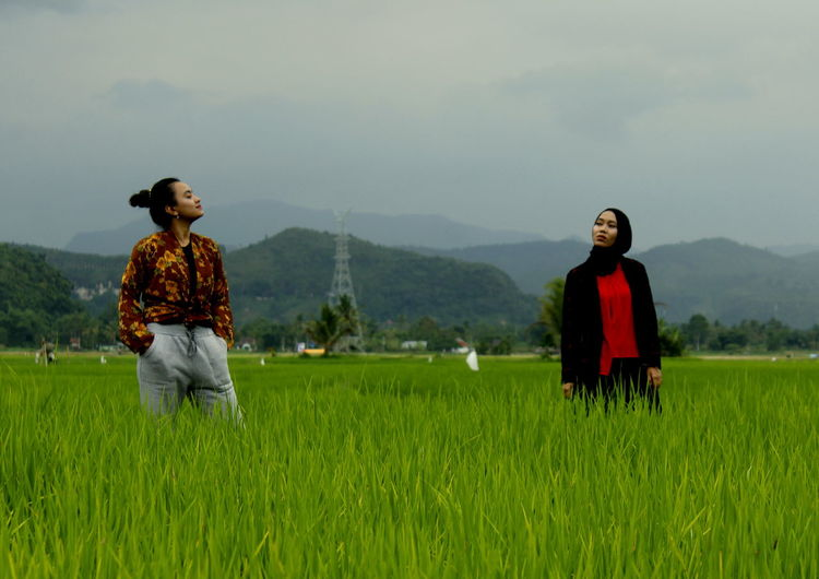 Women standing on field against sky