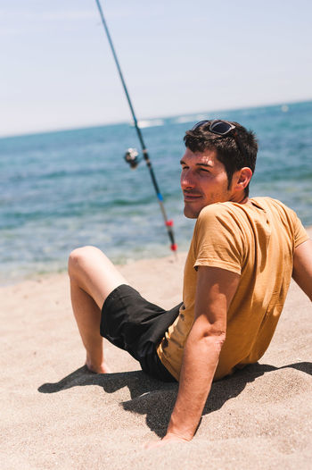 Young man sitting on shore at beach against sky