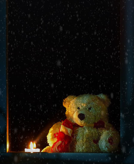 Teddy Bear By Lit Candle Seen Through Window Glass During Winter