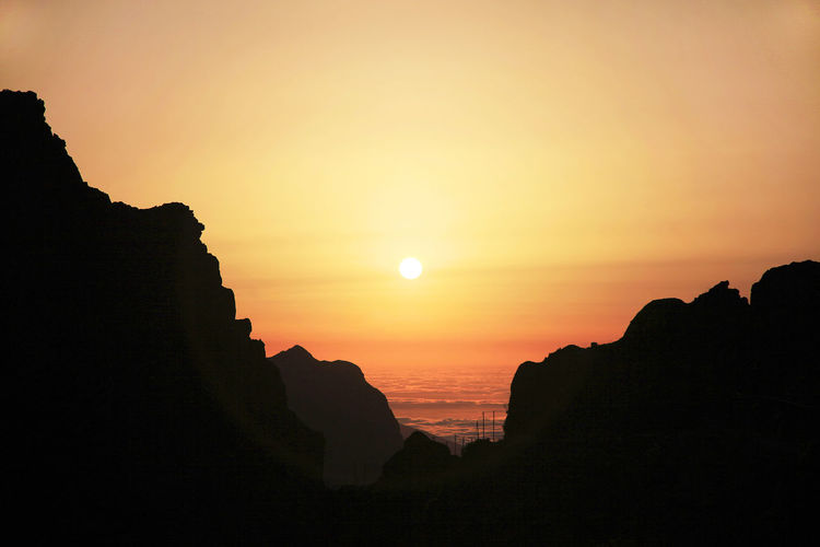 Silhouette cliff by sea against orange sky