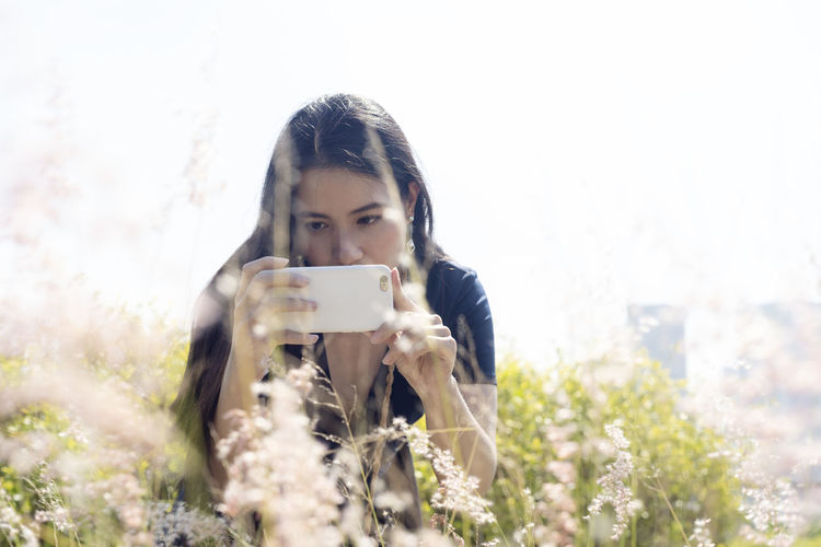 Portrait of young woman photographing through mobile phone