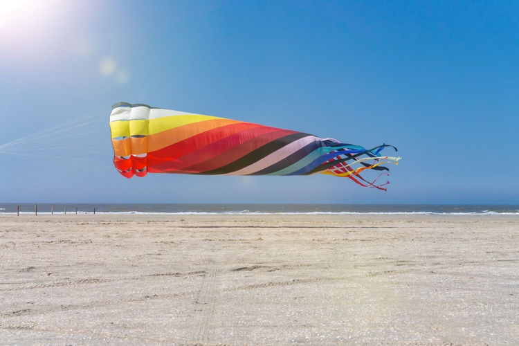 Low angle view of multi colored kite at beach against blue sky