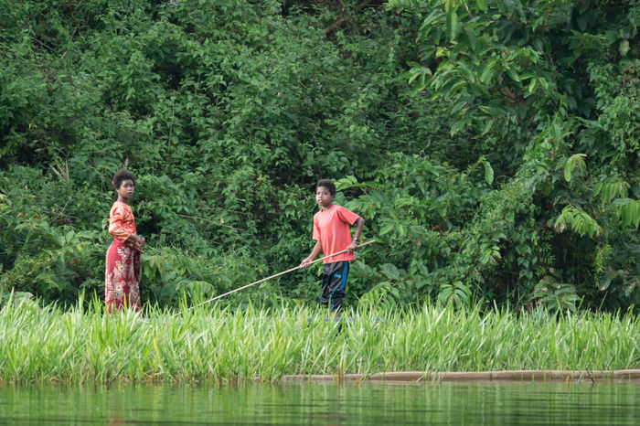 PERAK, MALAYSIA - 19TH MARCH 2017; A daily life of Jahai tribe in Royal Belum Rainforest Park, existence for over 130 million years making it one of the world's oldest rainforest. Aborigines Childhood Day Full Length Grass Green Color Growth Hapiness Indigenous People Lake Lake View Mature Adult Nature Nature Only Men Outdoors People Purity Rainforest Royal Belum State Park Simple Things In Life Standing Togetherness Tree Two People