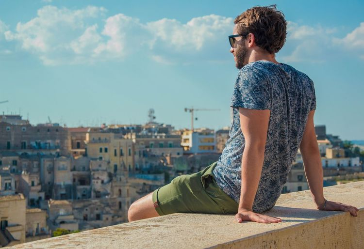 Young man sitting on retaining wall against sky