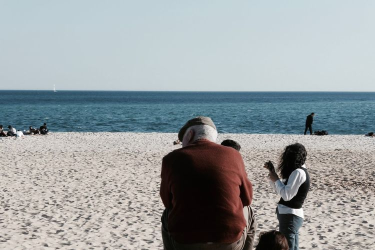 Rear view of people on calm beach against clear sky