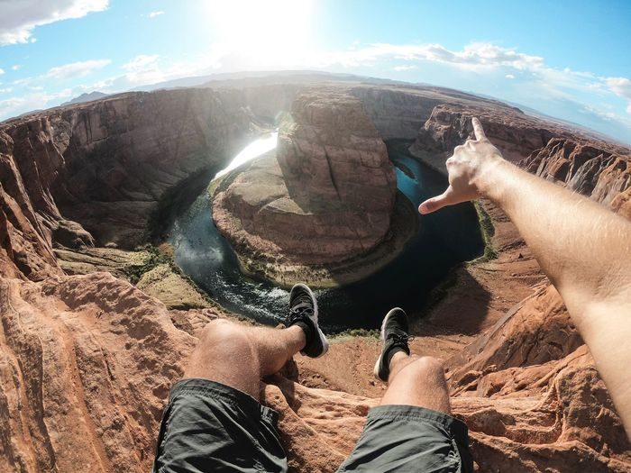Low section of man gesturing against horseshoe bend